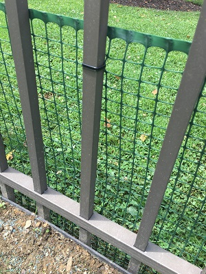 Wrought iron style fencing with plastic mesh reinforcement to prevent escape between the bars.